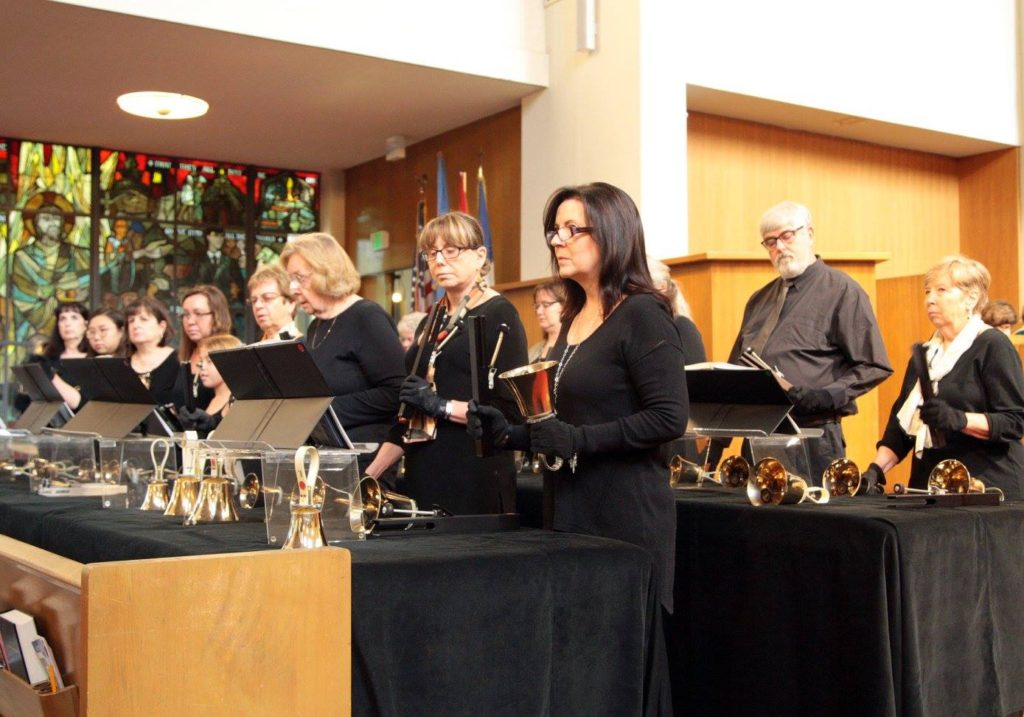 A group of people dressed in all black, playing hand bells.