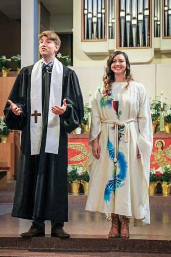 Pastors Jen and Jacob, wearing robes, smiling, and addressing the congregation