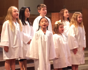 A group of young children wearing white robes and singing.
