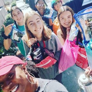 Members of our youth group, smiling for the camera and holding up supplies they are taking to donate.