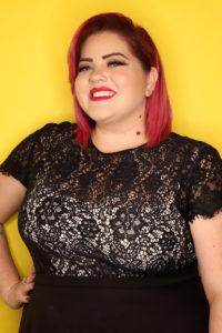 Jr. High Youth Director Zoe Estrada, wearing a black lace shirt and smiling at the camera