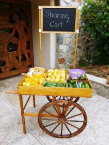 """A wooden """"Sharing Cart"""" filled with fresh produce."""