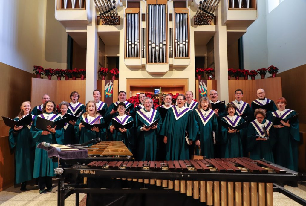 Members of the Chancel Choir wearing robes, singing, and smiling at the camera