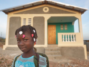 A young girl smiles at the camera, standing in front of a newly built house