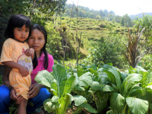 A woman and child kneel and look at the camera amidst a growing garden