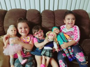 Three immigrant children, sitting on a couch and holding dolls, smiling and laughing.
