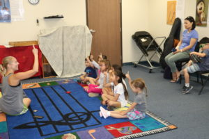 A group of young children sit on the floor and watch their music instructor