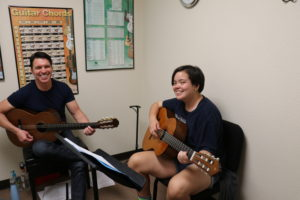 An instructor and student hold guitars and smile at the camera